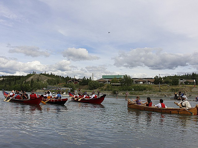 A flotilla of traditional watercraft takes to the Yukon River